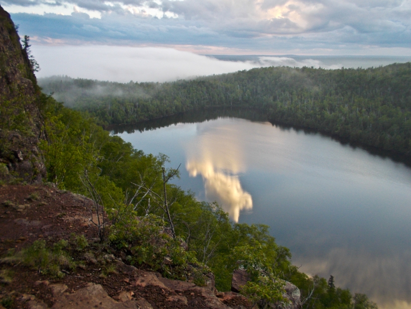 The clouds reflect off the glasslike surface of the lake as the fog moves through a valley to the south