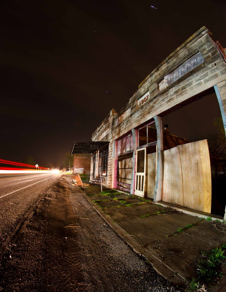 Traffic speeds down Hwy. 77 next to an abandoned building in Forreston, TX as the stars shine and the clouds sweep across the sky on a warm night in early March